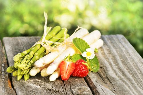 Leinwanddruck Bild Asparagus, Spargel, grün und weiß, Bund, mit Erdbeeren, auf Holz, Textraum, copy space
