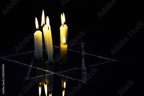 Five burning candles and the Star of David against a black background.