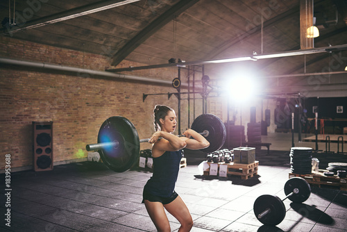 Poster Young muscular female lifting barbells in gym