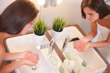 Young woman washing her face with clean water in bathroom - 183957421
