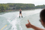 woman riding on wave of motorboat in a summer lake - 183959234