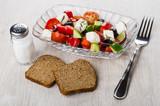 Greek salad in transparent bowl, salt, bread and fork - 183963275