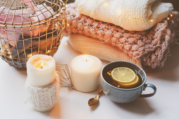 Cozy winter morning at home. Hot tea with lemon, knitted sweaters and modern metallic interior details. Still life composition, danish hygge concept