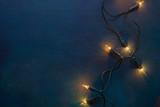 Christmas garland lights on vintage dark wooden background - 183967895