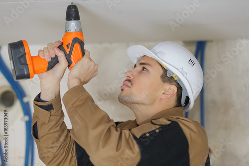 construction builder drilling ceiling