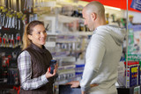smiling young woman helping customer household store - 183973459