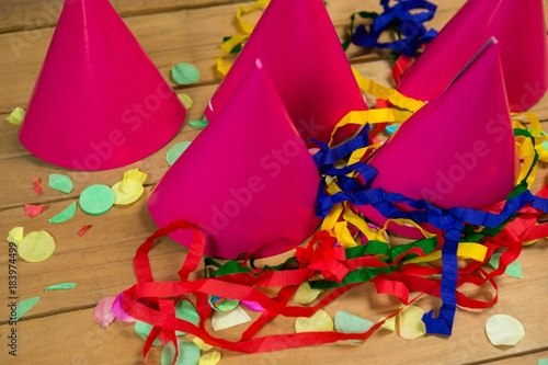 Party hats with streamers and confetti on wooden surface