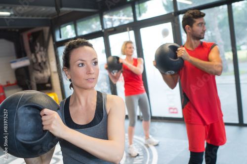 Poster People in fitness class holding round prop