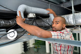 Man holding flexible hose in roofspace - 183976010