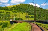 railroad viaduct through forested hills in summer. lovely transportation scenery in Carpathian mountains, Skotars'ke, Ukraine - 183978483