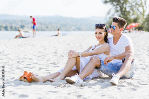 Romantic young couple sitting at a beach