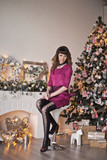 The woman in Magenta short dress near Christmas tree and fireplace 957