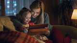 Beautiful Mother and Her Little Daughter are Sitting on a Sofa in the Living Room, They Use Tablet Computer. It's Evening, Room is Cozy and Warm. - 183992852