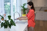 Woman washing fruit in kitchen