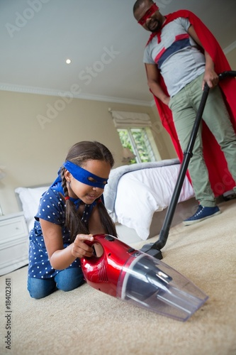 Father and daughter in superhero costume and cleaning a floor Poster
