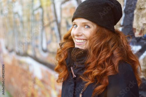 Foto op Canvas Graffiti lachende frau mit mütze und warmer jacke steht draußen in der stadt