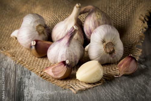 Close-up garlic bulbs and garlic cloves on wooden background - 184029281
