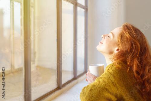 Leinwanddruck Bild schöne frau genießt die sonnenstrahlen am fenster