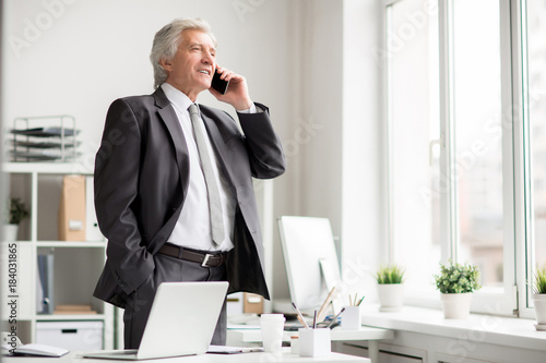 Confident mature businessman with smartphone phoning to one of subordinates by his workplace