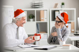 Aged boss in Santa cap giving small box with xmas surprise to one of his subordinates during work