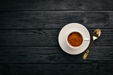 A cup of espresso coffee on a dark wooden background. Top view. Free space for text. - 184036432
