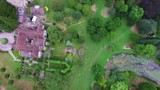An aerial shot of lawn mowers on a backyard of a brick house. The shot is far up. - 184040437