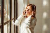 Joyful woman listening to music near window - 184042604
