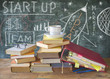 Drawing of a Start up concept on black board w. books, file folders, office supplies