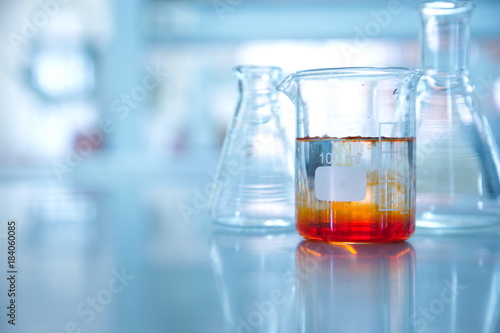 orange solution in beaker and flask in chemistry science laboratory background