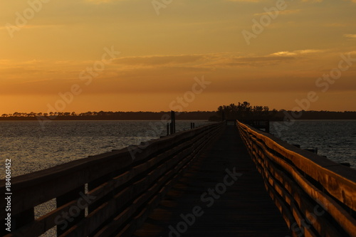 Tuinposter Bruin Wooden fishing pier jetty after sunset