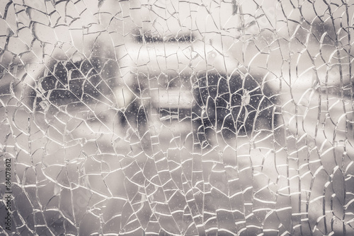 Broken glass and blurred city background - 184078612