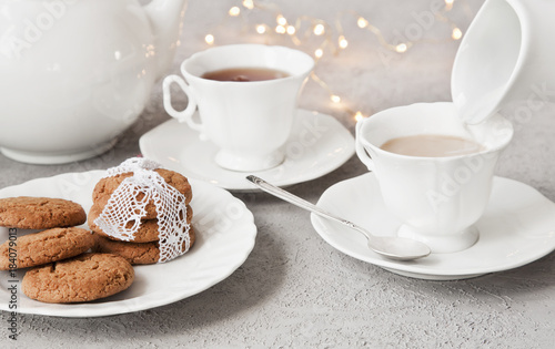 Wall mural Close-up of white cups of coffee with milk and chocolate cookies on table in vintage style background