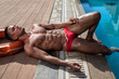 Muscular young sexy wet lifeguard in swimming trunks with red lifebuoy outdoors near pool