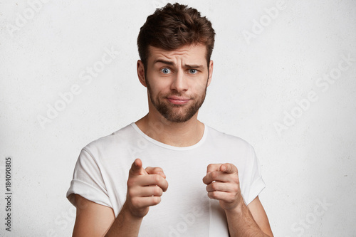 Pleasant looking bearded male with trendy hairdo indicates with index fingers directly at you, has puzzled expression, isolated over white concrete background. Attractive man chooses someone
