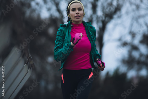 Poster Woman jogging outside in cold winter day