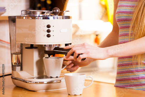 Wall mural Woman in kitchen making coffee from machine