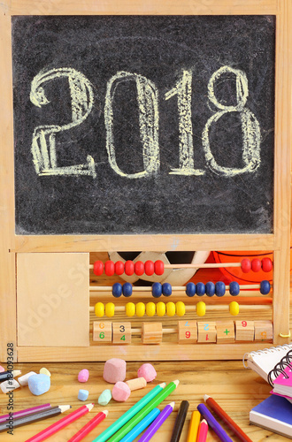 Small black board in wooden abacus frame and hand written 2018 new year greeting on it. Scattered stationery, colorful pencils, chalks, bounded note books on wooden table - 184093628