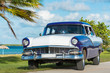 Постер, плакат: Amerikanischer blau weisser Ford Fairlane Oldtimer parkt am Strand unter Palmen in Varadero Cuba Serie Cuba Reportage