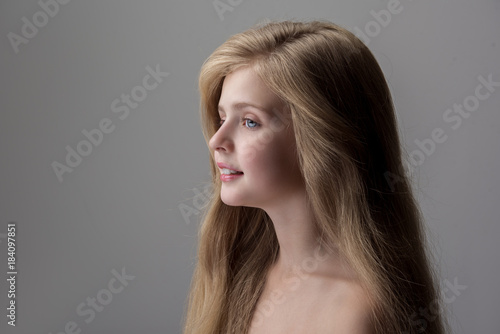 In de dag Spa Enjoying day. Side view of joyful lovely little girl is standing with naked shoulders and looking forward with slight smile. Isolated background with copy space in the left side