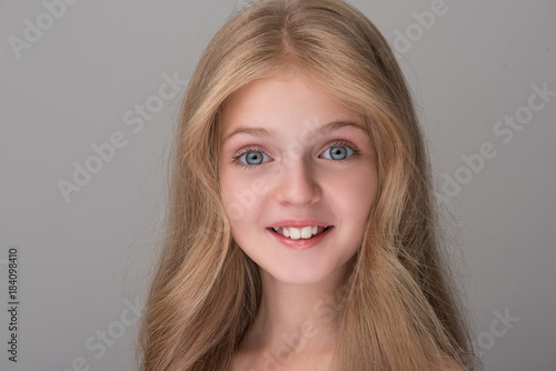 Feeling excited. Close-up portrait of cheerful amazed pretty girl is standing and looking at camera in wide-eyed surprise and smiling. Isolated background