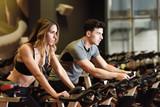 Couple in a spinning class wearing sportswear. - 184122287