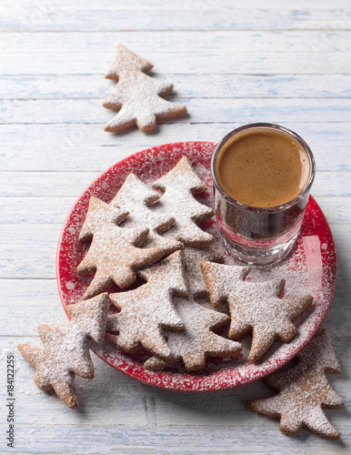 Wall mural Oatmeal gingerbread cookies in the shape of Christmas tree on a red plate sprinkled with powdered sugar with a coffee shot on a light blue background, top view