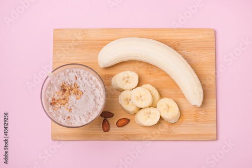 Foto op Plexiglas Milkshake Fresh made banana smoothie in a glass on pink background