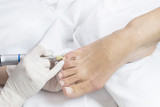 Female foot in the process of pedicure procedure in a beauty salon close-up. - 184135885