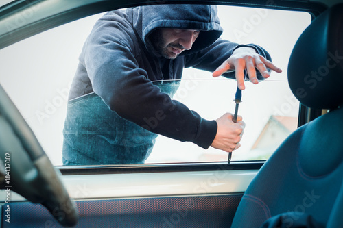 Sticker Thief breaking the car window to steal one car