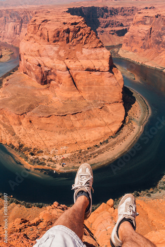 Fotobehang Koraal Young man standing by the edge of the Horse Shoe Bend cliff. Celebrating happy successful life.