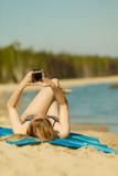 Woman in bikini sunbathing and relaxing on beach - 184158810