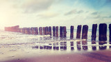 Vintage toned picture of an old wooden breakwater on a beach at sunset, nature background.