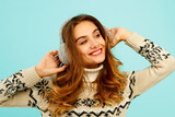 Pretty young woman in warm sweater over blue background - 184168228