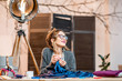 Young female fashion designer working with blue fabric sitting at the beautiful office with different tailoring tools on the table